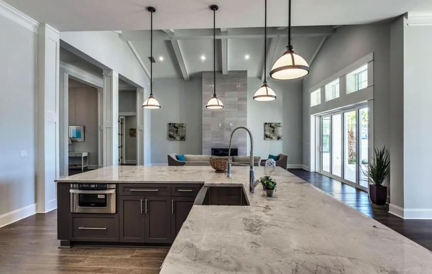 Transitional kitchen with brazilian arabescato quartzite counter, custom island, classic pendant lights and white oak hardwood floors