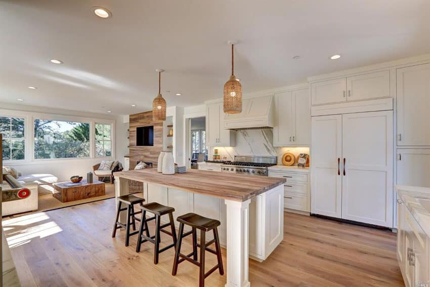 Transitional kitchen with calacatta white marble counters, butcher block island and wide plank hardwood flooring