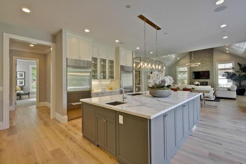 Transitional kitchen with carrara white marble counter island, white oak wood floors and two color cabinets
