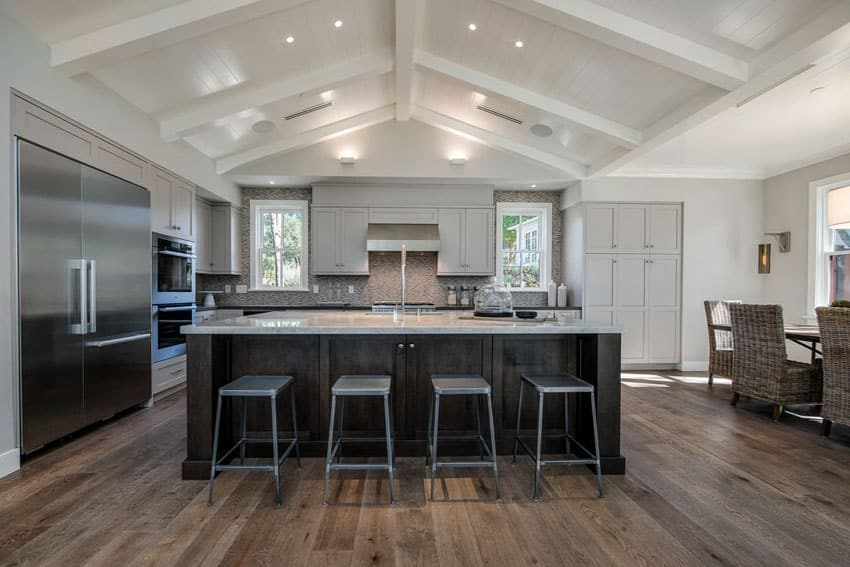 Transitional kitchen with cathedral ceiling, large rectangular island and wide plank wood floors