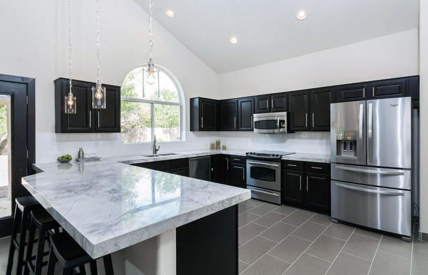 Transitional kitchen with dark cabinets, dining peninsula and calacatta carrara marble counter