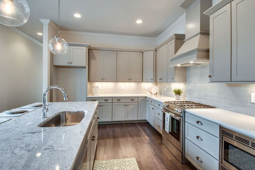 Transitional kitchen with gray cabinets, arctic white quartz, snowfall granite countertops, subway tile and globe pendant lights