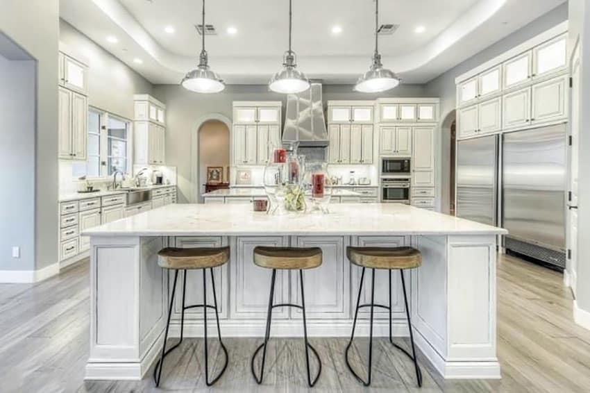 Transitional kitchen with white cabinets, breakfast bar, porcelain tile floors and industrial dome shape pendant lights
