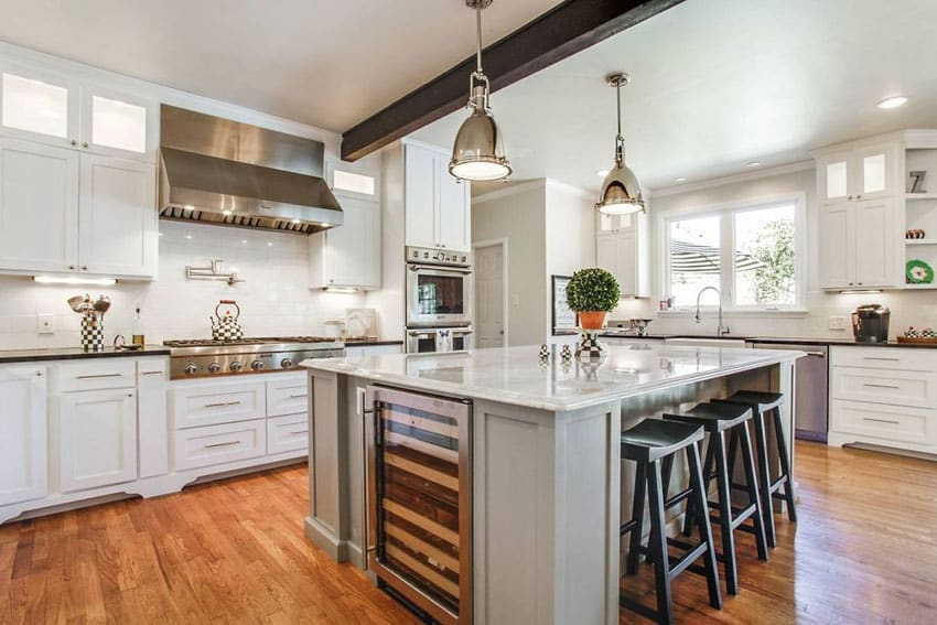 transitional-Kitchen with white cabinets, thassos subway tile backsplash, nickel pendant lights and marble counter island with breakfast and bar black bar stools