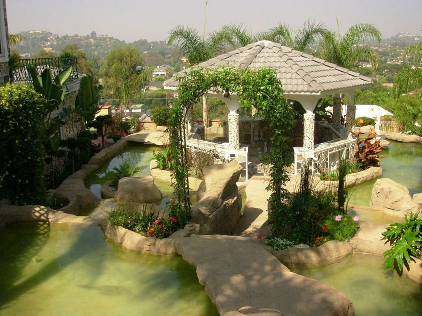 Tropical garden with white gazebo and vine arch pathway past pond
