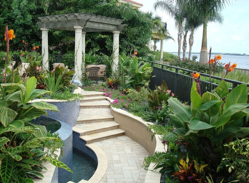 Tropical landscaped garden with path to pillar pergola