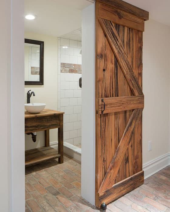 Weathered sliding barn door leading to bathroom