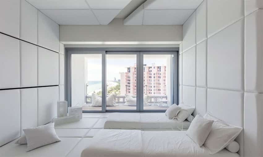 Japanese inspired white bedroom with tufted walls and balcony view of ocean