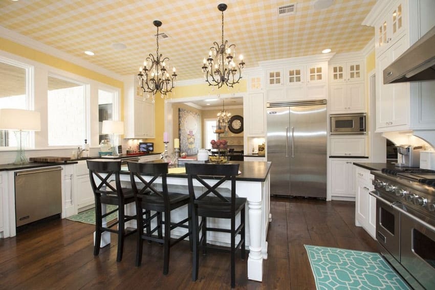 White cabinet country style kitchen with yellow walls and dark wide plank floors