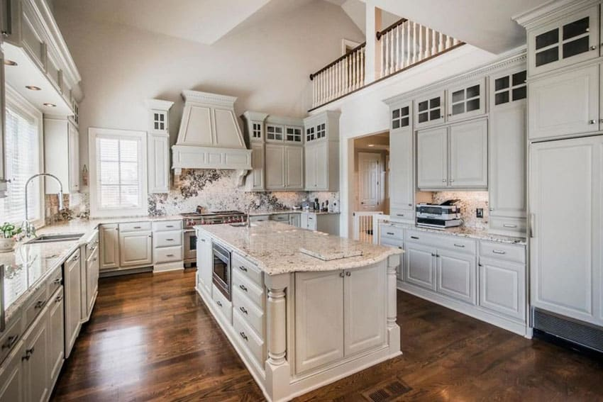 White cabinet kitchen with alpine white granite counter and backsplash open to second story balcony