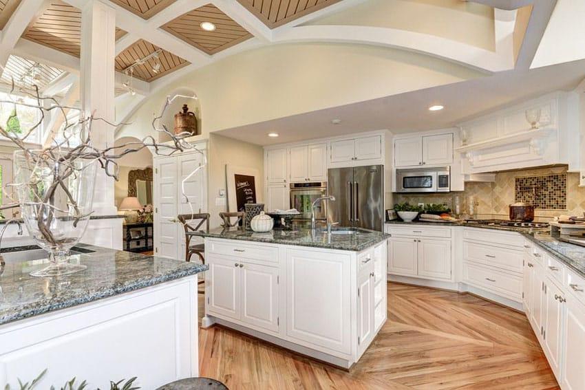 White cabinet kitchen with crema perla granite counters, center island and american walnut flooring
