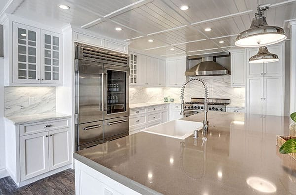 White cabinet kitchen with quartz and marble countertops and chrome pendant lights