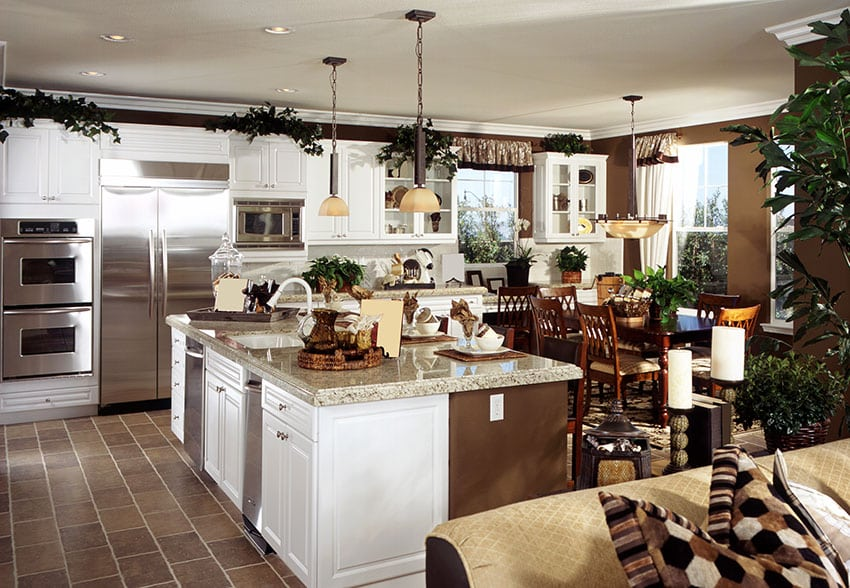 White cabinet kitchen with transitional design, brown color theme and light beige granite island