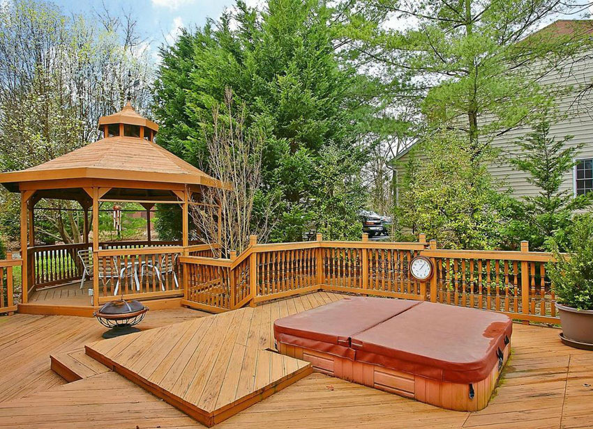 Wood deck with gazebo and spa in backyard of home
