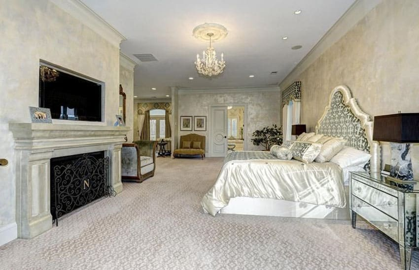 Beautiful bedroom with custom bed, mirrored furniture, chandelier, fireplace and fire screen