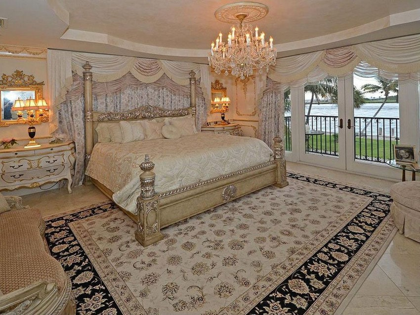 Bedroom with decorative bed french provincial furniture, chandelier and water front views