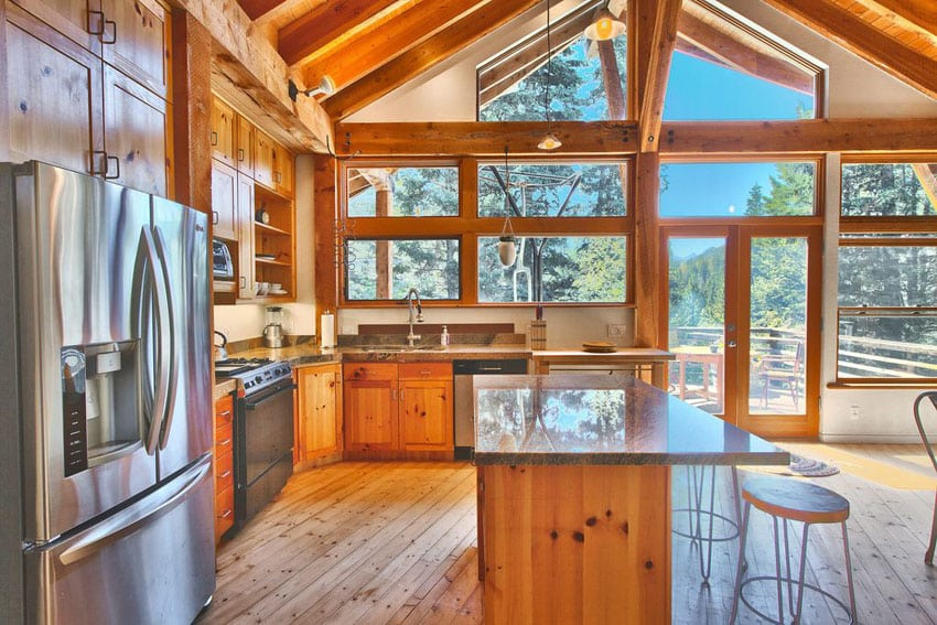 Bright rustic wood cabinet kitchen at mountain cabin with lots of natural light
