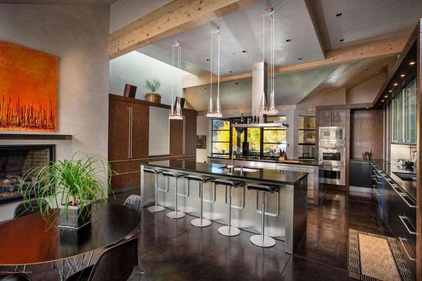 Modern rustic kitchen with concrete floors, exposed beams, black counters and piston chrome bar stools