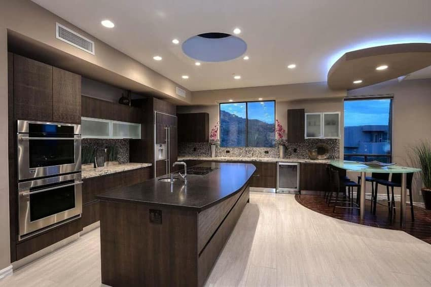 Contemporary kitchen with dark brown cabinets glass counter peninsula