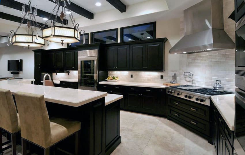 Contemporary kitchen with dark cabinets limestone floors and breakfast bar island