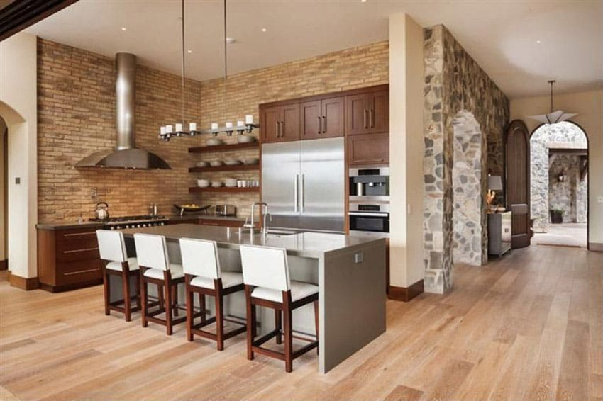 Modern rustic style kitchen with gray graphite counters, large breakfast bar island and brick veneer walls