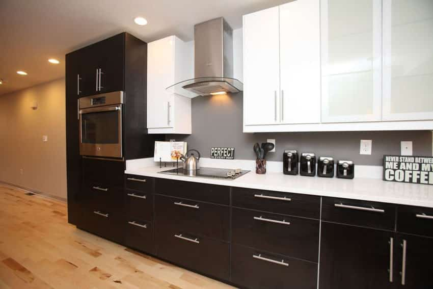 Contemporary one wall kitchen with arctic white quartz countertops and black and white cabinets