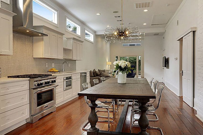 Contemporary one wall kitchen with white cabinets, wood floors and wood dining table