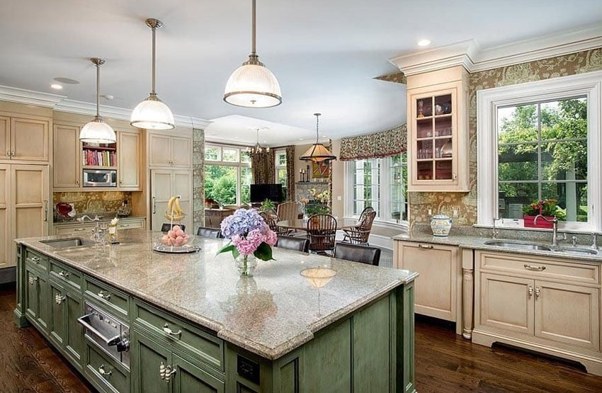 Country kitchen with green island cream color cabinets wood floors and patterned wallpaper