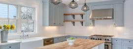 country-kitchen-with-light-blue-cabinets-single-basin-farmhouse-sink-viking-range-and-wood-counter-island-painted-white