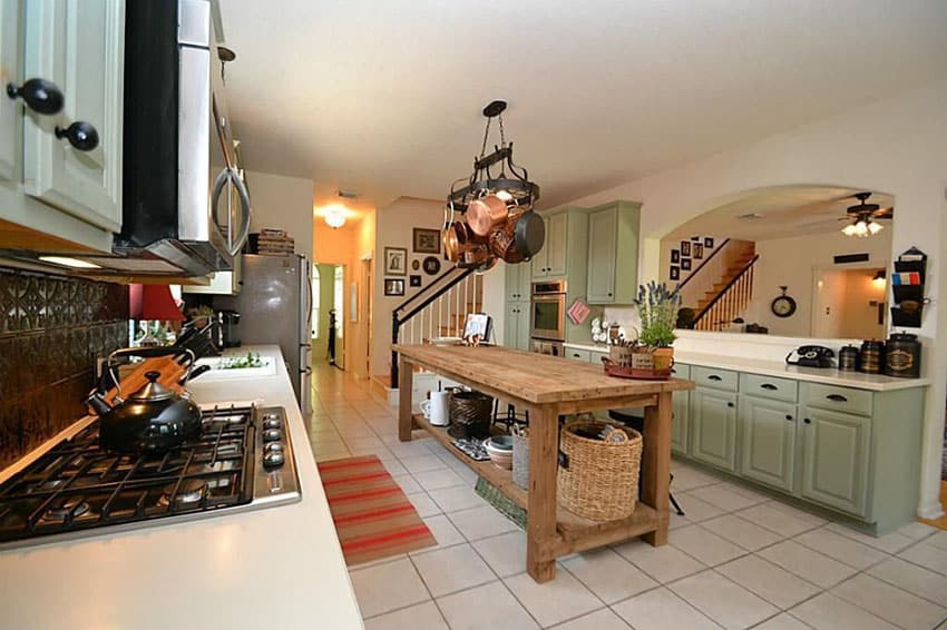 Country kitchen with light green cabinetry, brushed bronzed backsplash and rustic wood island