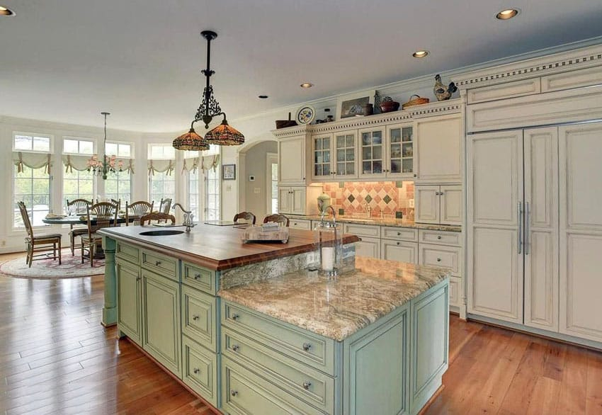 Country kitchen with light green two tier island with butcher block counter and typhoon bordeaux granite