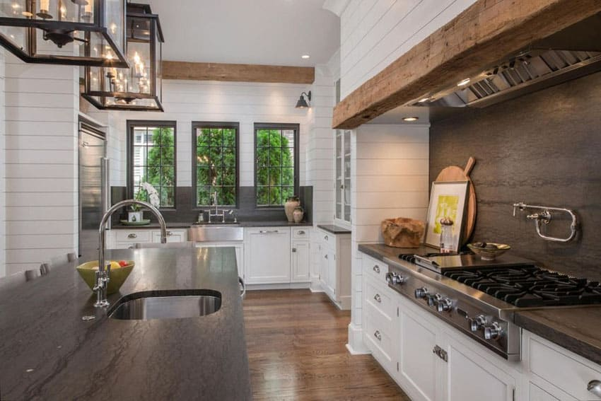 Country kitchen with white cabinets shiplap board walls and black soapstone countertops
