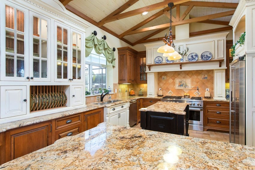 Country style kitchen with rustic white cabinet uppers and brown lower cabinets and beige granite island