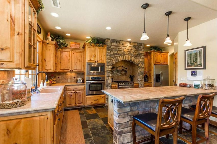 Craftsman kitchen with limestone counter island and custom stone oven surround