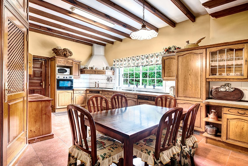 Farmhouse kitchen with exposed beam ceiling, wood dining table and rustic cabinets