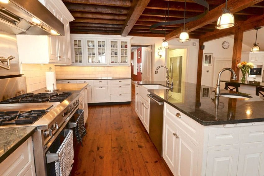 Modern farmhouse kitchen with white cabinets, blue pearl silver granite countertop and wide plank hardwood floors