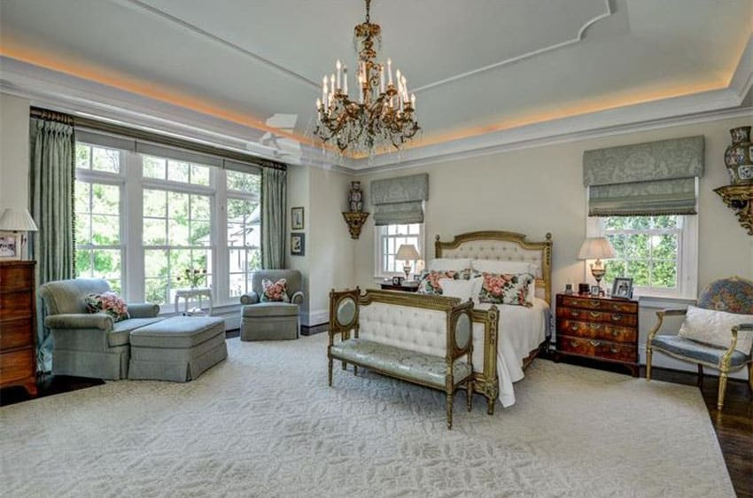 French provincial bedroom with tufted bed, chandelier, lounge chair, tray ceiling and vintage furniture