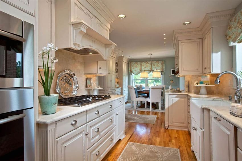 Galley style farmhouse kitchen with basin sink white cabinets and wood floors