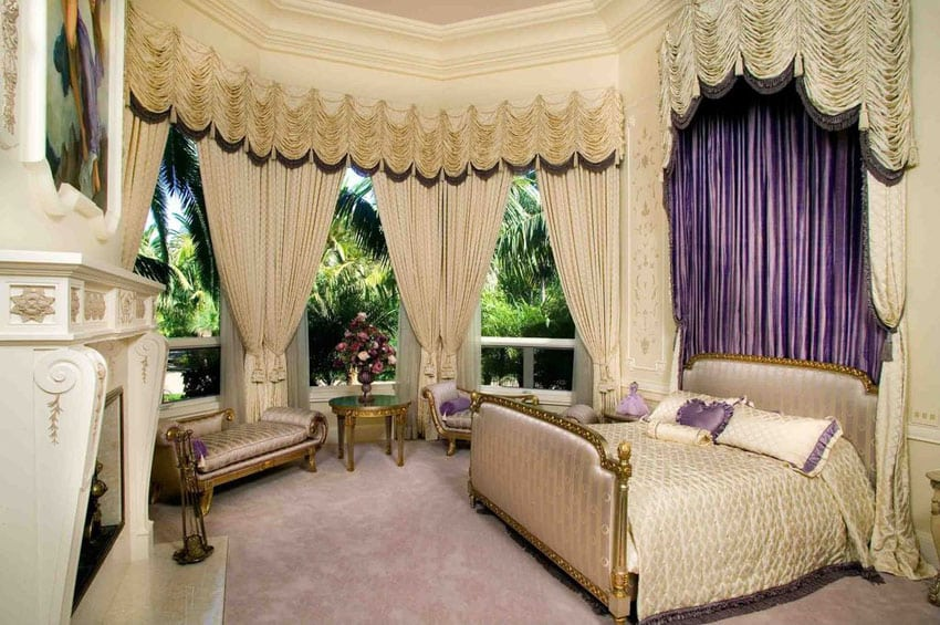 Gorgeous bedroom with gilded gold bed frame, bed drapery, large windows, gold furniture pieces and fireplace
