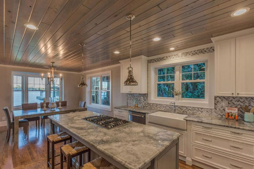 Gorgeous rustic contemporary kitchen with white cabinets, island with built in cooktop and wood plank ceiling