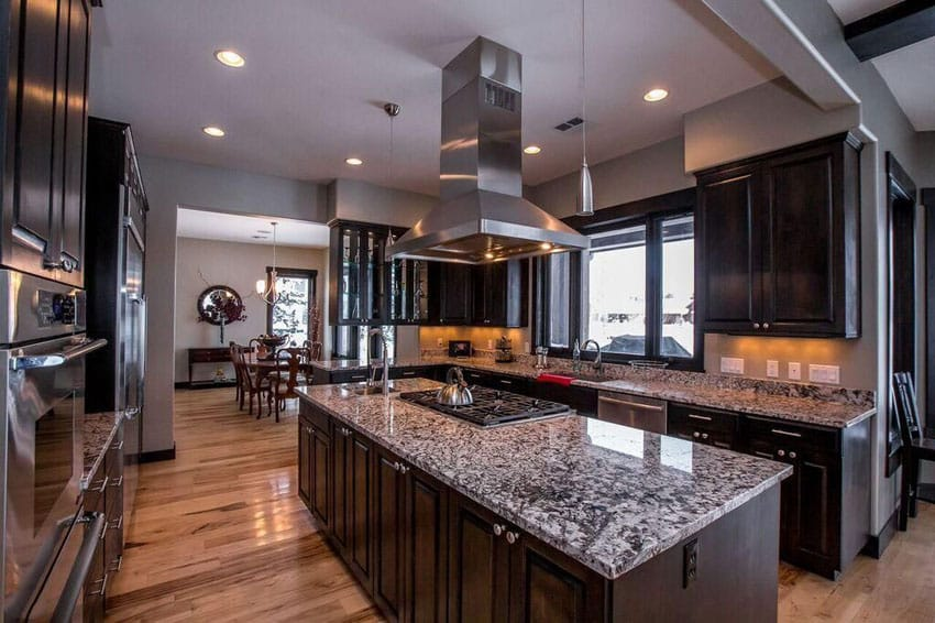 Kitchen with dark raised panel cabinets, center island with range and white wave granite counter