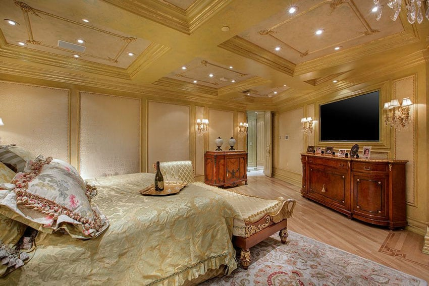 Luxurious master bedroom with gold decor, chaise lounge and rich wood furniture