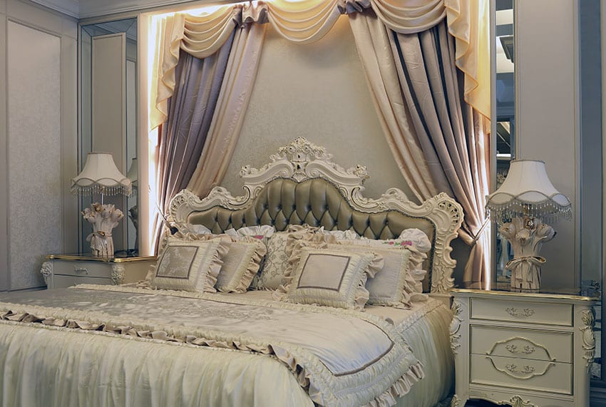 Luxury Parisian style bedroom with antique off white furniture, flowing curtains and tufted bed