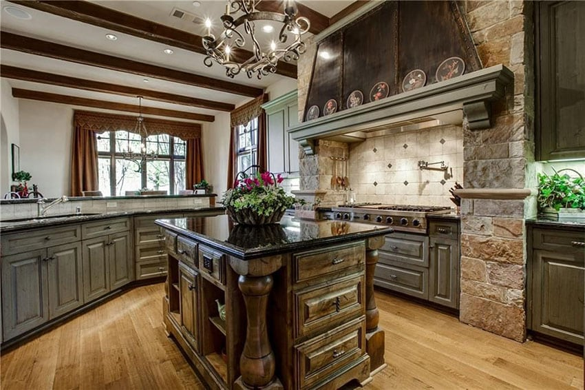 Luxury traditional kitchen with raised panel dark cabinets with antique black granite counter stone oven surround and island