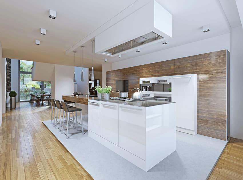 Modern dark wood cabinet one wall kitchen with white island and light wood flooring