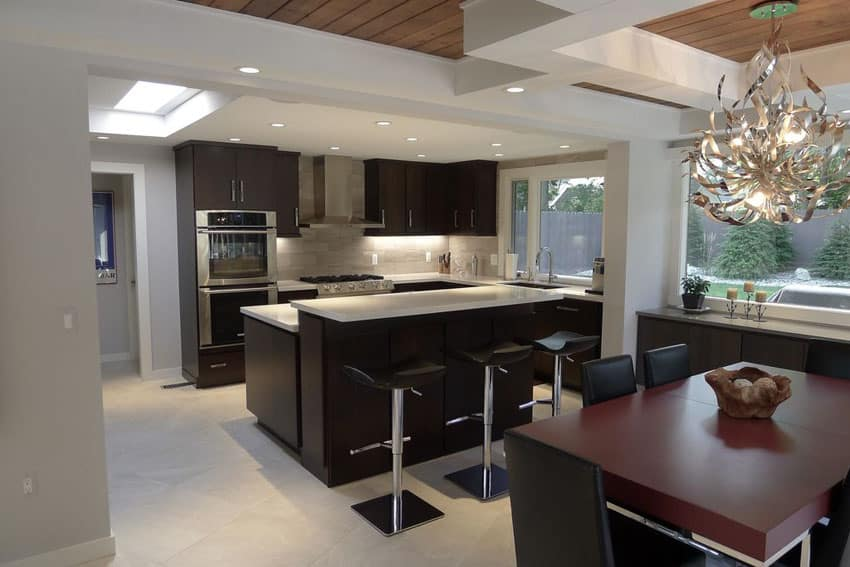 Modern kitchen with dark cabinets, split level light counter breakfast bar and open layout