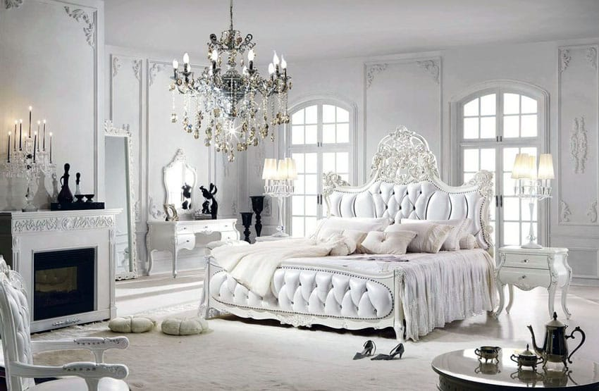 Romantic bedroom with European style tufted bed, fireplace, chandelier and white french provincial furniture