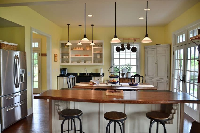 Rustic country kitchen with open shelved cabinets and bare wood breakfast bar