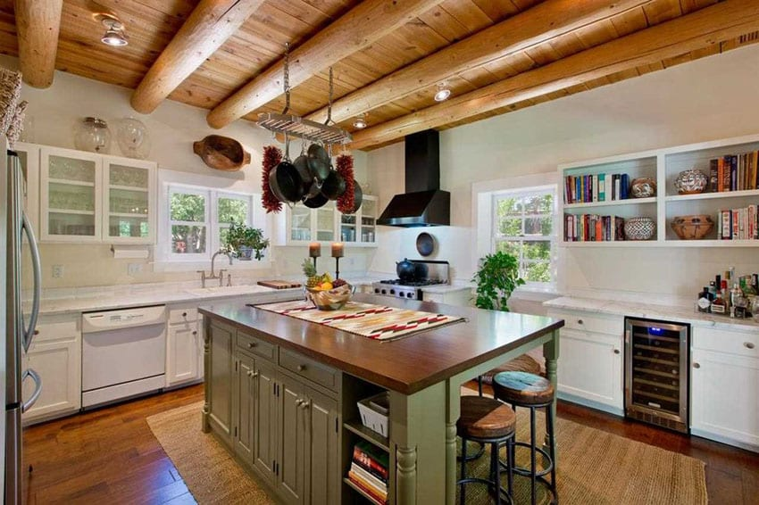 Kitchen with rustic wood countertop on green cabinet island, white cabinets and large round exposed beam ceiling