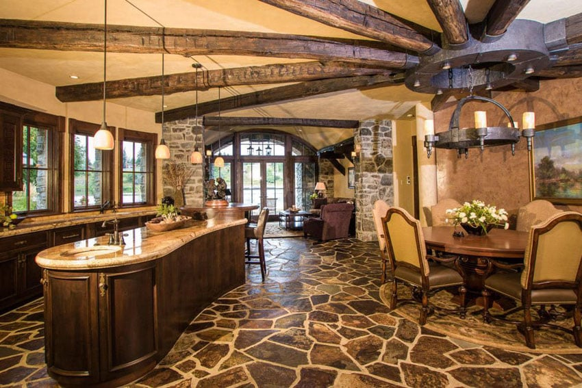 Rustic kitchen with rounded island topped with colonial cream granite and 12 light wrought iron chandelier